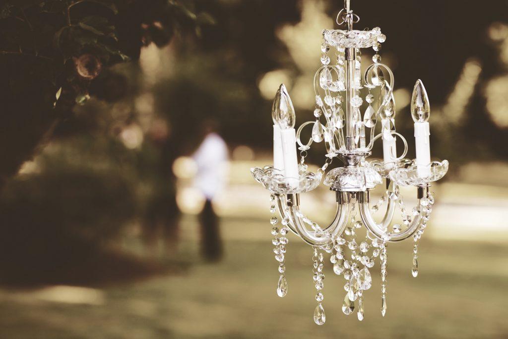 Kryształowy żyrandol powieszony na gałęzi podczas wesela plenerowego w ogrodzie
