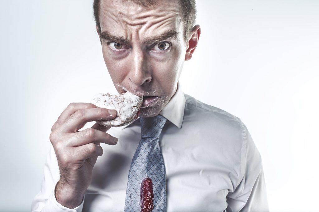 Mężczyzna jedzący pączka